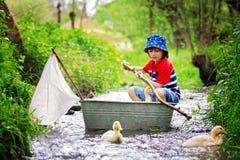 逗人喜爱的孩子,男孩,使用与小船和鸭子在一条小的河 库存图片