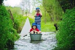 逗人喜爱的孩子,男孩,使用与小船和鸭子在一点riv 免版税库存照片