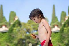 逗人喜爱的孩子,男孩,吃在海滩的新月形面包 免版税库存图片