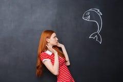 逗人喜爱的害怕妇女在黑板背景画的惊吓了鲨鱼 免版税库存图片