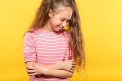 逗人喜爱的害羞的微笑的女孩窘迫儿童情感 库存图片