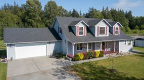 逗人喜爱的家外部与红色快门在一个夏日 免版税图库摄影