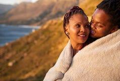 逗人喜爱的富感情的人种间夫妇保持温暖与毯子户外 图库摄影