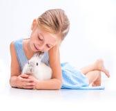逗人喜爱的小女孩一只白色兔子 库存照片
