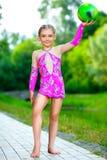 年轻逗人喜爱的小女孩体操运动员室外画象  免版税库存图片