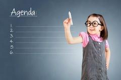 逗人喜爱的小女孩佩带的企业礼服和写空白的议程名单蓝色背景 免版税库存照片