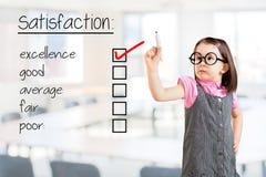 逗人喜爱的小女孩佩带的企业礼服和检查优秀在用户满意调查形式 办公室背景 免版税库存图片