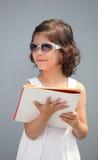 逗人喜爱的小女孩佩带的太阳镜和微笑 库存照片