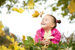 逗人喜爱的小女孩使用与叶子在公园 免版税库存照片
