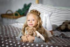 逗人喜爱的小女孩使用与玩具涉及床 库存照片