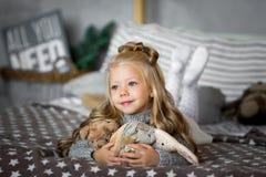 逗人喜爱的小女孩使用与玩具涉及床 免版税库存图片