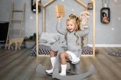 逗人喜爱的小女孩使用与玩具涉及床 库存图片