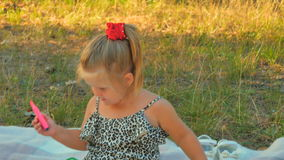逗人喜爱的小女孩使用作为毯子的金融家在公园 股票录像