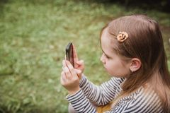 逗人喜爱的小女孩使用巧妙的电话 在背景的草 在女孩一把簪子用南瓜 图库摄影