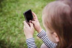 逗人喜爱的小女孩使用巧妙的电话 在背景的草 免版税图库摄影