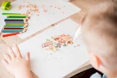 逗人喜爱的小女孩做补花胶合五颜六色的房子,应用颜色纸使用胶浆,当做艺术和工艺在幼儿园或h时 免版税库存图片
