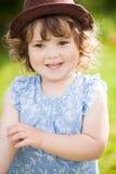 逗人喜爱的小女孩卷毛头发金发碧眼的女人在公园 免版税库存照片