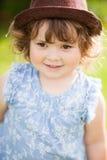 逗人喜爱的小女孩卷毛头发金发碧眼的女人在公园 免版税库存图片
