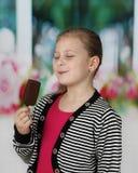 逗人喜爱的小女孩吃冰淇凌 免版税图库摄影