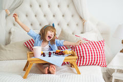逗人喜爱的小女孩吃和在床上的哈欠 图库摄影