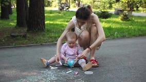 逗人喜爱的小女孩和她的母亲图画与白垩在边路在夏天停放 家庭、母性和人概念 股票录像