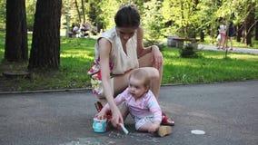 逗人喜爱的小女孩和她的母亲图画与白垩在边路在夏天停放 家庭、母性和人概念 股票视频