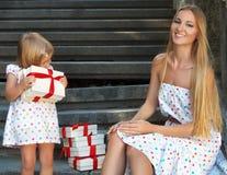 逗人喜爱的小女孩和她的母亲藏品礼物 免版税库存照片