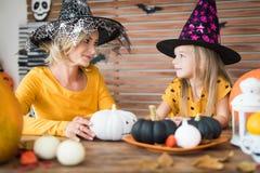 逗人喜爱的小女孩和她的母亲,两个在巫婆服装,坐在万圣夜题材的一张桌后装饰了室,微笑 库存图片