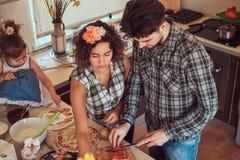 逗人喜爱的小女孩和她美好的父母准备薄饼,当在家时烹调在厨房里 库存图片