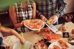 逗人喜爱的小女孩和她美好的父母准备薄饼,当在家时烹调在厨房里 免版税库存图片