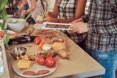 逗人喜爱的小女孩和她美好的父母准备薄饼,当在家时烹调在厨房里 库存照片