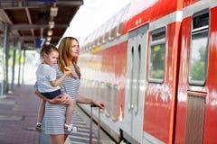 逗人喜爱的小女孩和母亲一个火车站的 库存图片