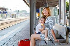 逗人喜爱的小女孩和母亲一个火车站的 免版税库存照片