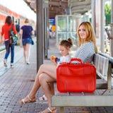 逗人喜爱的小女孩和母亲一个火车站的 免版税库存图片
