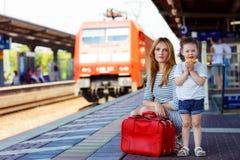 逗人喜爱的小女孩和母亲一个火车站的 库存照片