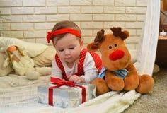 逗人喜爱的小女孩和玩具鹿在圣诞树下 婴孩在她的手上的拿着一件礼物 图库摄影