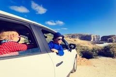 逗人喜爱的小女孩和男孩乘汽车旅行  库存照片
