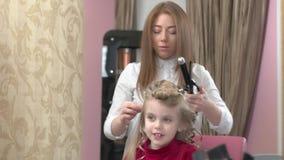 逗人喜爱的小女孩和美发师 股票录像