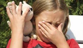 逗人喜爱的小女孩哭泣与玩具 免版税库存照片