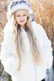 逗人喜爱的小女孩在冬天穿衣户外 免版税库存照片