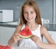 逗人喜爱的小女孩在厨房里吃一个西瓜 免版税库存照片