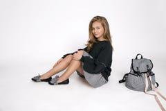 逗人喜爱的小女孩在学校衣裳和学校背包开会穿戴了 免版税库存照片