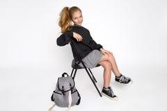 逗人喜爱的小女孩在学校衣裳和学校背包开会穿戴了 免版税库存图片