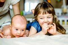 逗人喜爱的小女孩在家使用与他的说谎在床上的弟弟 库存照片