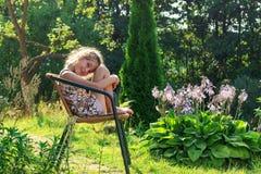 逗人喜爱的小女孩在庭院里在温暖坐并且微笑着 库存图片