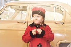 逗人喜爱的小女孩在摆在老朋友汽车附近的减速火箭的外套穿戴了 免版税库存照片