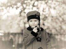 逗人喜爱的小女孩在摆在老朋友汽车附近的减速火箭的外套穿戴了 库存图片