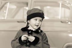 逗人喜爱的小女孩在摆在老朋友汽车附近的减速火箭的外套穿戴了 库存照片