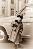 逗人喜爱的小女孩在摆在老朋友汽车附近的减速火箭的外套穿戴了 免版税库存图片