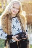 逗人喜爱的小女孩在有照相机的湖附近休息 免版税图库摄影